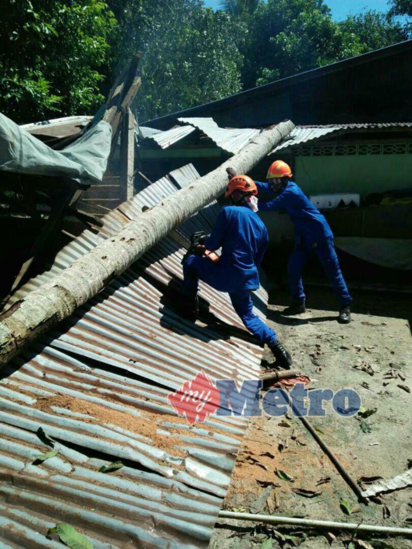 ANGGOTA APM sedang memotong dan membersih rumah Nordin Mat Saman yang dihempap pokok kelapa di Kampung Tembak B, Parit Panjang. FOTO Ihsan APM