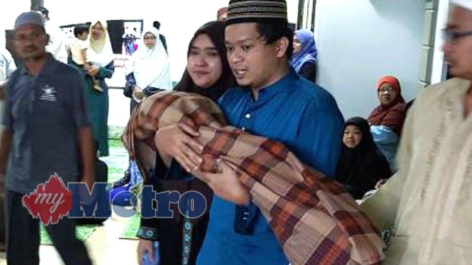 MOHD Haniff Selaman @ Sulaiman, 28, memangku jenazah anaknya, Ahnaf Hanafi Mohd Hanif untuk dikebumikan di Tanah Perkuburan Islam Jalan Bukit Ubi, Kuantan. FOTO Raja Norain Hidayah Raja Abdul Aziz