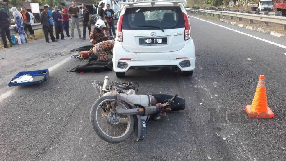 ANGGOTA bomba berusaha membantu mengeluarkan penunggang motosikal yang terperosok di bawah kereta Perodua Myvi dalam kemalangan di Kilometer 22 Lebuhraya Utara Selatan, arah selatan dekat Asun. FOTO Ihsan Pembaca