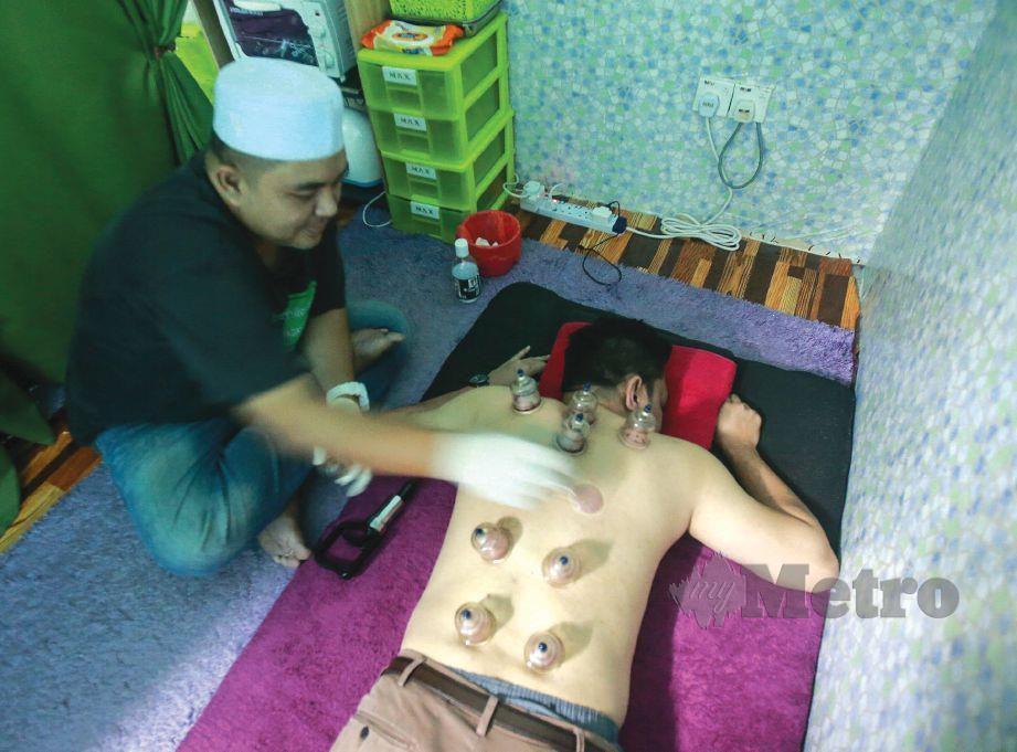 AHMAD berpengalaman 12 tahun sebagai jurubekam, melekatkan bekas di badan pelanggan.