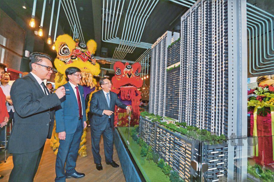 LEONG (kanan) dan Ho (tengah) melihat replika rumah pada majlis pelancaran galeri jualan M Arisa, semalam.