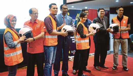 TIMBALAN Naib Canselor (Jaringan Industri dan Masyarakat), Dr Renuganth Varatharajoo (tengah) menyampaikan helmet dan jaket keselamatan.