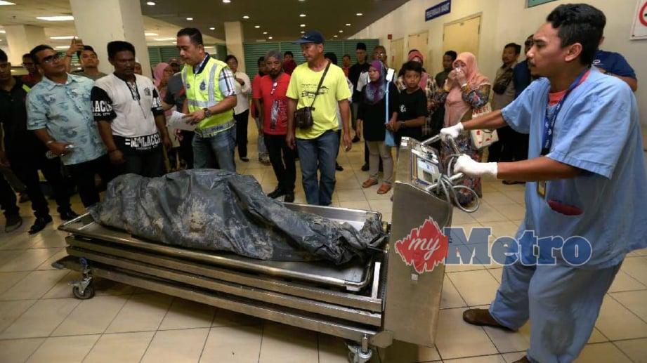 ANGGOTA Polis Diraja Malaysia (PDRM) membawa mayat keempat Jeleha Hashim, 48 yang lemas di Jambatan Kampung Paya Jaras untuk proses bedah siasat di Jabatan Forensik Hospital Sungai Buloh. FOTO Zunnur Al Shafiq