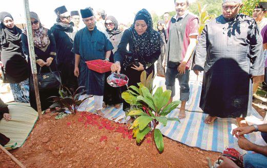 ANAK Allahyarham Julie Dahlan, Nur Haslinda Zainuddin (tengah) menyiram pusara ibunya di Tanah Perkuburan Islam Klang Gate.