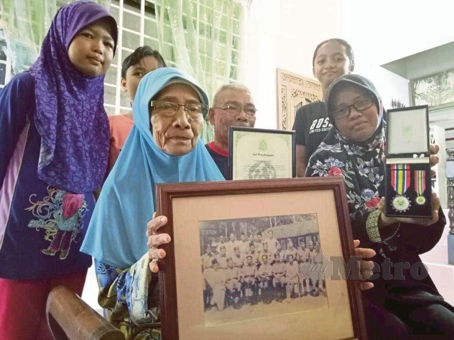 JAMILAH menunjukkan gambar anggota Balai Polis Bukit Kepong termasuk bapanya, Abu Bakar yang  diserang pengganas komunis pada 23 Februari 1950.