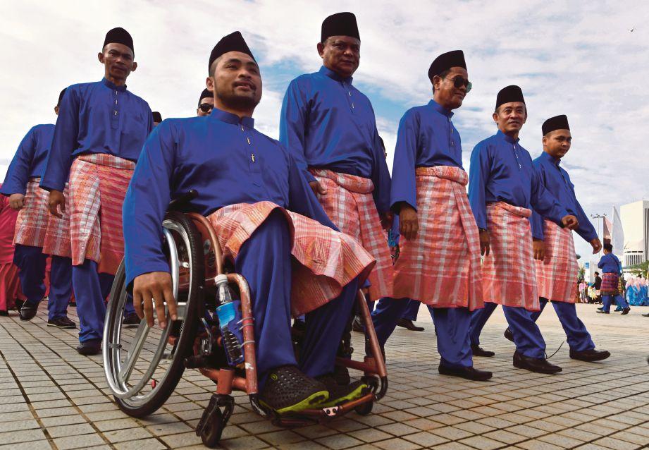 Walaupun berkerusi roda seorang peserta bersemangat menyertai perarakan di Sarawak.