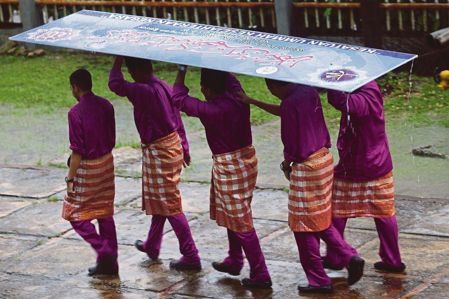 Sebahagian peserta perarakan meredah hujan semasa hadir sambutan Maulidur Rasul di Terengganu.