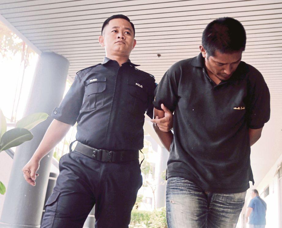 NORIZAM (kanan) diiringi anggota polis keluar dari Mahkamah Majistret Ayer Keroh, semalam.