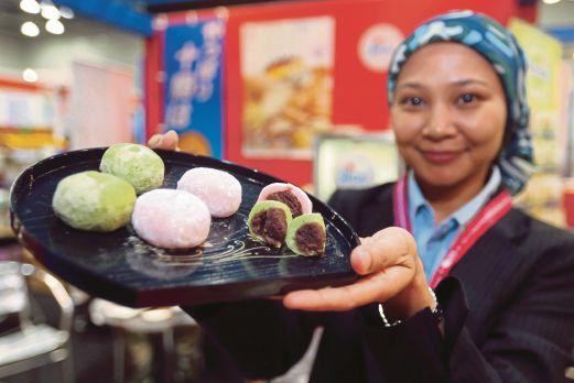 Siti Azmila Abd Aziz menunjukkan makanan tradisional negara Jepun, Mochi yang dijual pengusaha Jepun di negeri Kedah ketika pameran halal antarabangsa Malaysia 2016 di Pusat Konvensyen Kuala Lumpur.