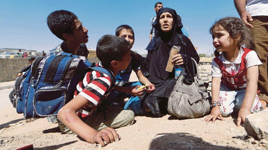 SATU keluarga yang melarikan diri dari daerah Zanjili tiba di kawasan yang dikuasai tentera kerajaan Iraq, semalam. - AFP