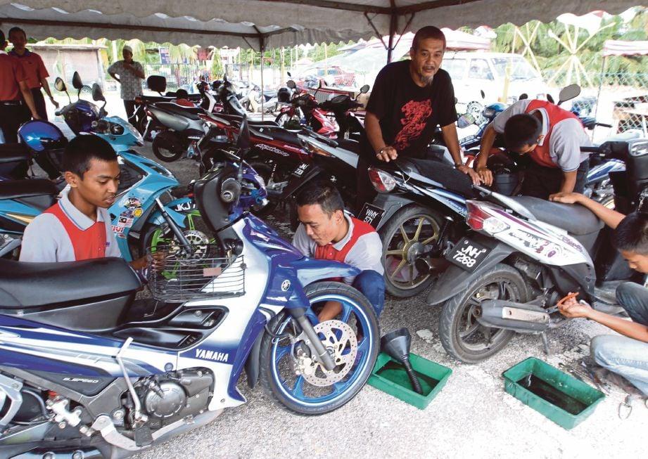 KHIDMAT pemeriksaan motosikal percuma oleh peserta GiatMARA sempena Program UMNO Bantu Rakyat 2.0 di Kampung Cokro.