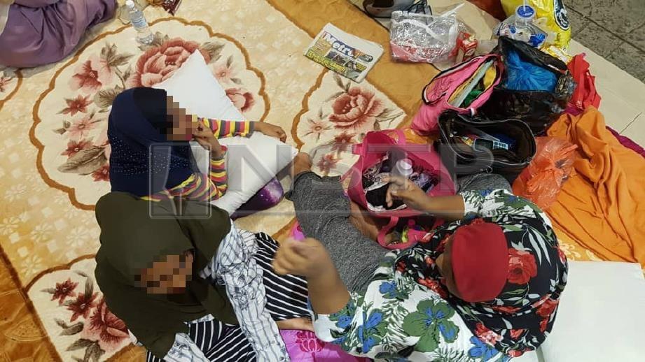 SEBAHAGIAN daripada lebih 20 penyewa Projek Perumahan Rakyat (PPR) Taman Manggis, Jalan Sultan Zainal Abidin, yang diusir dari rumah masing-masing sejak pagi semalam, masih 'berkampung' di perkarangan Kompleks Tun Abdul Razak (Komtar) dengan menjadikan kawasan itu sebagai rumah kedua kerana tiada tempat tinggal. FOTO Mikail Ong