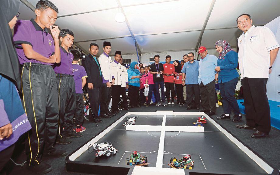 AHMAD Bashah (tiga dari kanan) menyaksikan pertunjukkan robotik  pada Pertandingan Robotik Dwengo Antarabangsa.