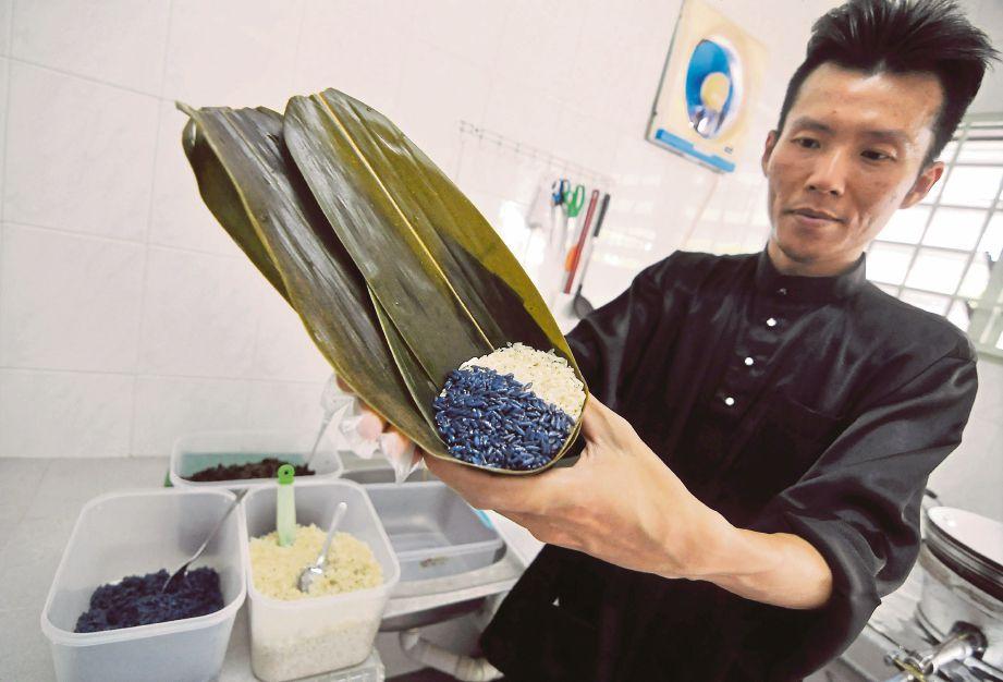 MARZUKI menunjukkan beras pulut biasa dan ungu yang diisi dalam daun buluh sebelum dibentuk segi tiga bagi menghasilkan kuih chang.