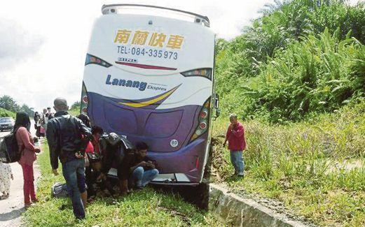 KEADAAN bas ekspres yang terbabas ke dalam semak.