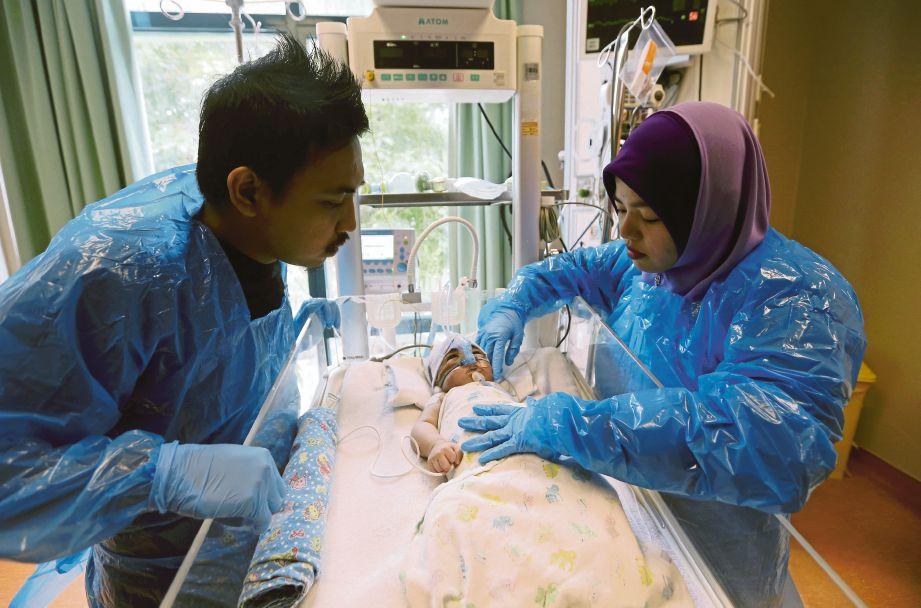 KHAIRIL Azwan dan Nur Ayuni melihat Muhammad Khayri Ammar  yang menghidap masalah injap terbalik.