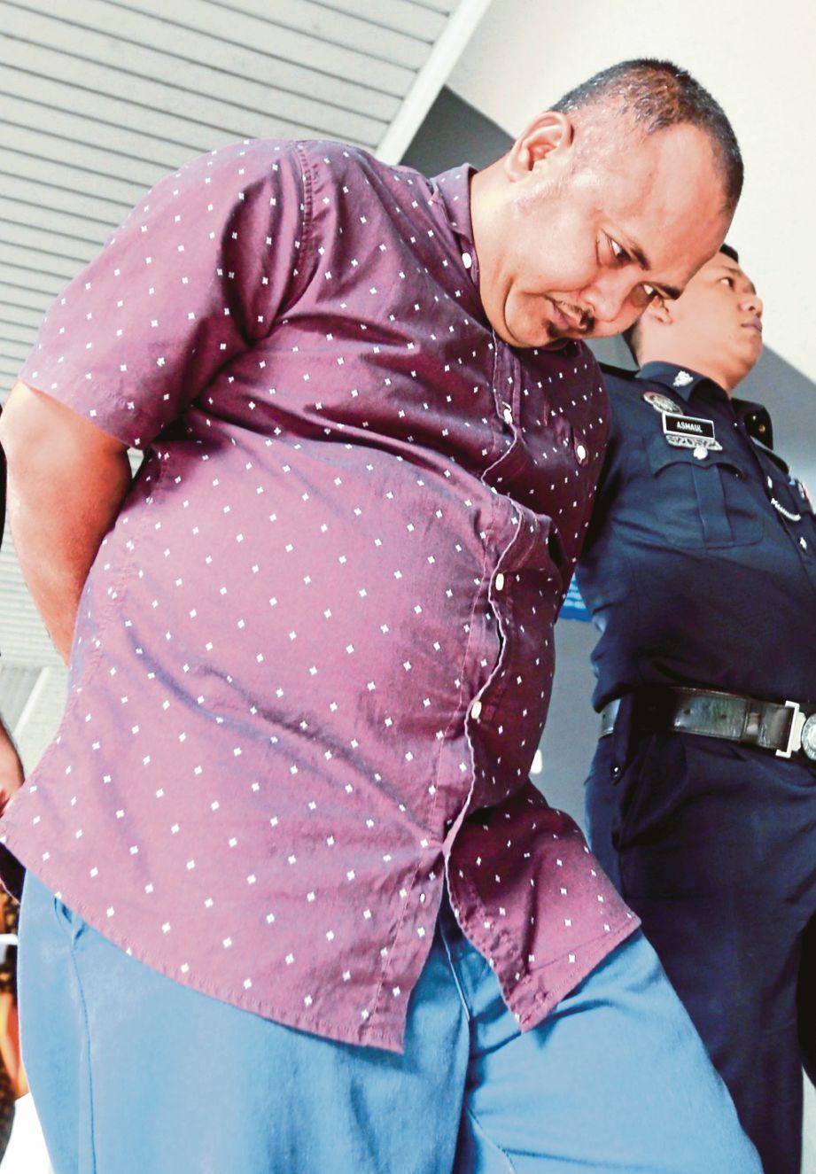 Abdul Razak diiringi polis keluar dari Mahkamah Sesyen Ayer Keroh, semalam.
