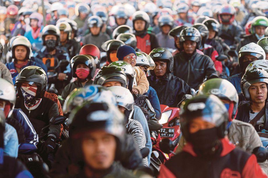 PENUNGGANG motosikal berbaris sambil menunggu feri melintas pulau Jawa di pelabuhan Gilimanuk, Bali ketika dalam perjalanan menyambut Aidilfitri dijangka Rabu ini. FOTO Agensi