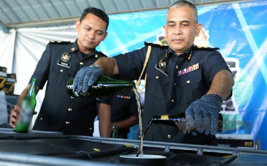 KETUA Pegawai Penguatkuasa KPDNHEP Negeri Sembilan, Johary Yacob melupuskan arak tiruan yang dirampas pada sidang media Pelupusan Ekshibit Barang Tiruan di Stor KPDNHEP Nilai. FOTO Hasriyasyah SABUDIN