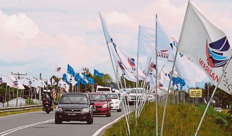 BENDERA Warisan dan Barisan Nasional menghiasi jalan di sepanjang Bengawan ke Membakut. FOTO Bernama