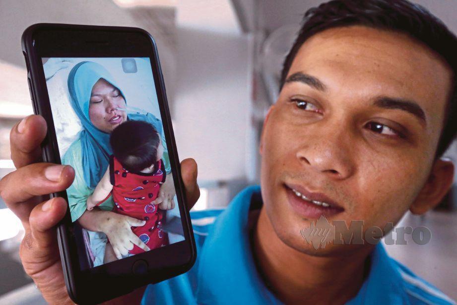 MOHD Saiful menunjukkan gambar kali pertama Norfadilla memangku anak mereka, Muhamad Syahmi.