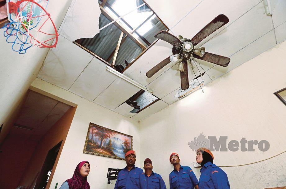 ANGGOTA APM melihat keadaan siling bumbung rumah mangsa yang rosak dipukul ribut di Taman Tunku Maheran.