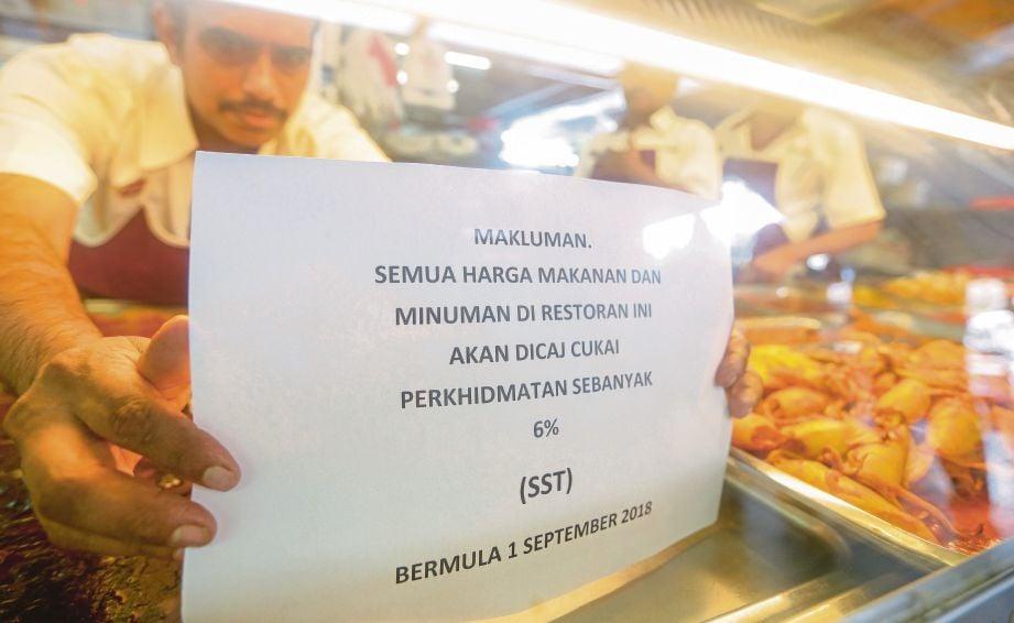 PEKERJA restoran mamak melekat notis pemberitahuan berkenaan caj SST yang berkuat kuasa pada 1 September lalu.