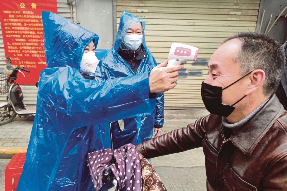 SEORANG pekerja memeriksa suhu badan lelaki di pintu masuk kawasan perumahan. FOTO Reuters