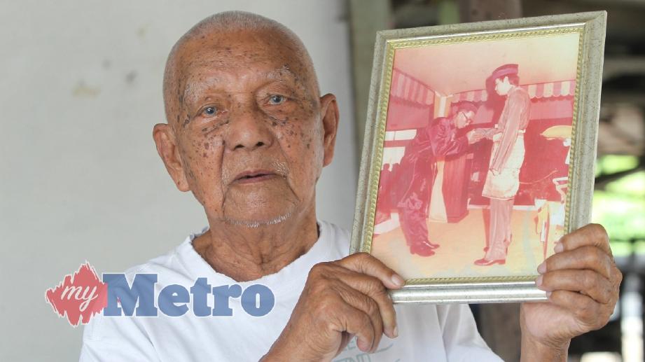 PENGUNDI tertua di kawasan Parlimen Klang, Surip Wasimin, 92 menunjukkan gambar Pingat Jasa Kebaktian (P.J.K) yang dianugerahkan oleh Sultan Selangor, Sultan Salahuddin Abdul Aziz Shah pada tahun 1980 ketika ditemui di rumahnya di Telok Gong, Klang. FOTO Intan Nur Elliana Zakaria