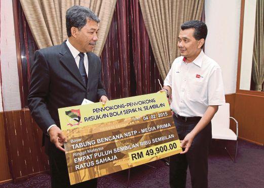 Mohamad (kiri) menyerahkan sumbangan Tabung Bencana NSTP-Media Prima kepada Amrin di Wisma Negeri, semalam.