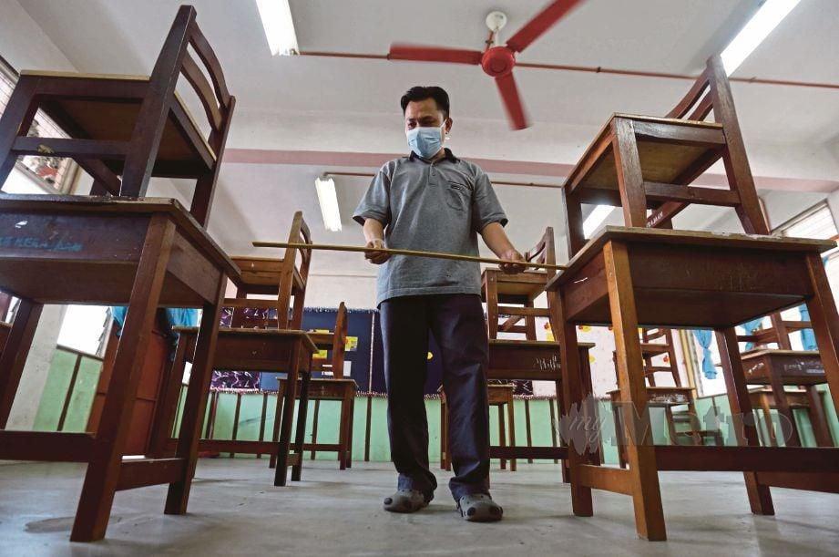 KAKITANGAN sekolah mengukur jarak di antara meja mengikut prosedur operasi standard (SOP). FOTO Mohamad Shahril Badri Saali