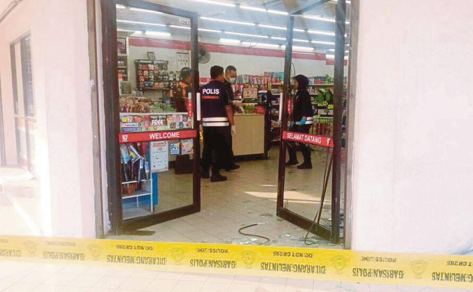ANGGOTA polis menjalankan siasatan di kedai serbaneka yang dirompak, semalam.