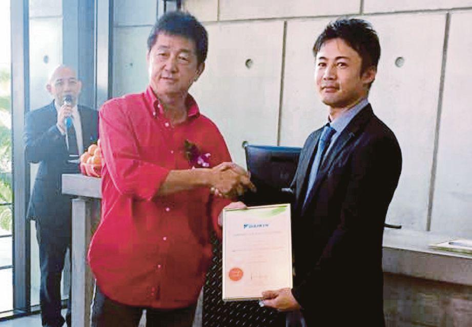 NORIAKI (kanan) menyerahkan Sijil Pengiktirafan 'Bangunan Daikin Eco' kepada Pengarah Urusan Inanam Properties, Ong Hock Lai.