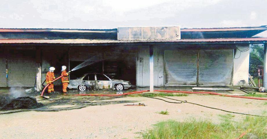 Anggota bomba   memadamkan kebakaran kedai di Jalan Hulu Sapi, Beluran, semalam.