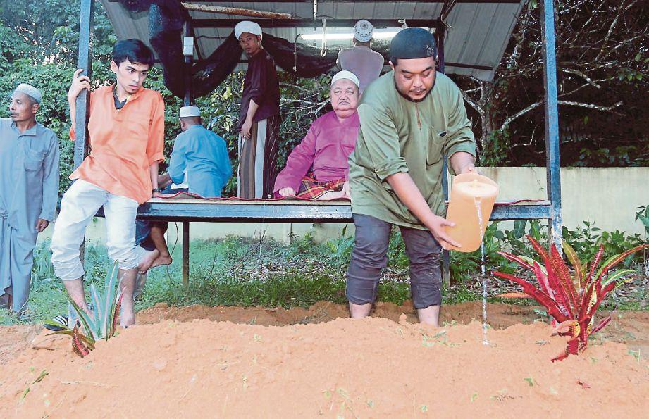 ISMA menyiram air mawar di pusara ibunya di Tanah Perkuburan Islam Kampung Padang Mengkali.