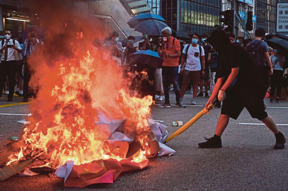 SEORANG penunjuk perasaan membakar  sepanduk ketika China menyambut 70 tahun pemerintahan Parti Komunis. FOTO EPA