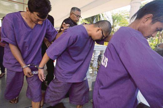 Tertuduh (tengah) yang terbabit dalam kes memenggal kepala seorang lelaki tahun lalu dibawa keluar dari Mahkamah Majistret Slim River.