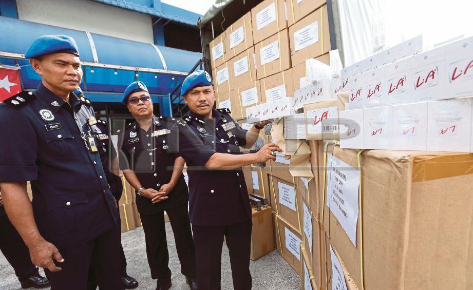 MOHD Yusoff (kanan) menunjukan rampasan rokok seludup yang dianggarkan bernilai RM1.42 juta dalam satu serbuan di Pantai Tanjung Kelisa, Kota Tinggi.