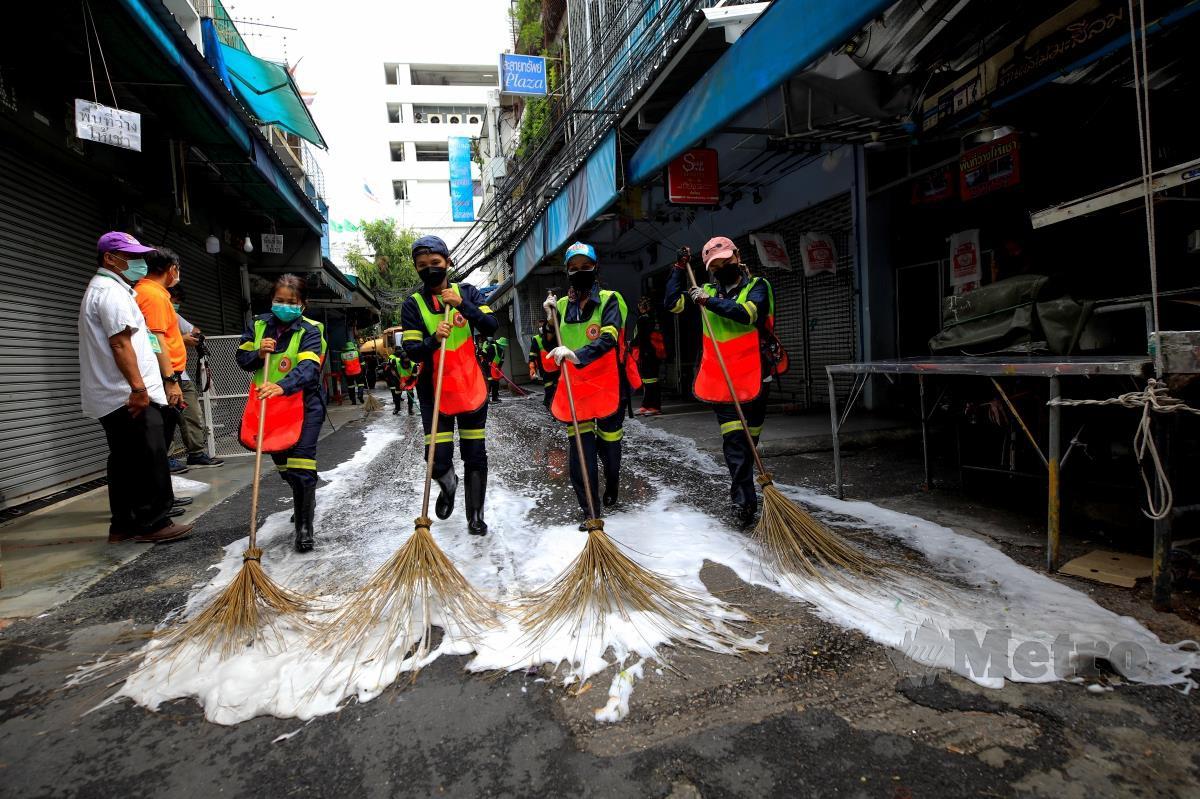Pekerja pembersihan membersihkan kawasan 'street market' di Bangkok. FOTO EPA