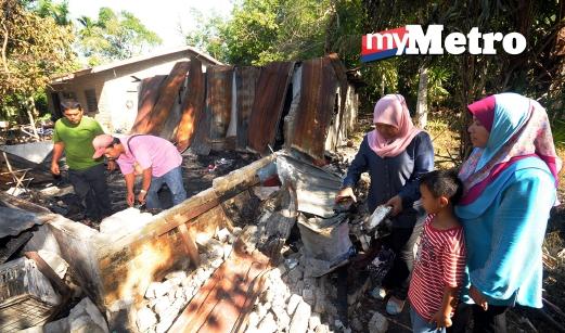 PEMANDU lori, Muhammad Khairul Faizal Abd Wahab, 28 (dua dari kiri) dan keluarganya memeriksa tapak rumah mereka yang musnah dalam kebakaran di Kampung Baru, Jalan Kilang Gula, Chuping, Perlis sehari sebelum puasa Ramadhan bermula. FOTO Hafizudin Mohd Safar