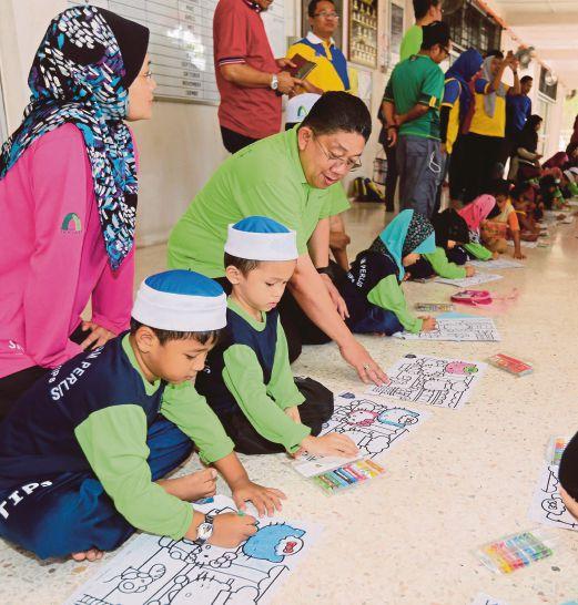 AB Latiff (tengah) melihat kanak-kanak menyertai pertandingan mewarna.
