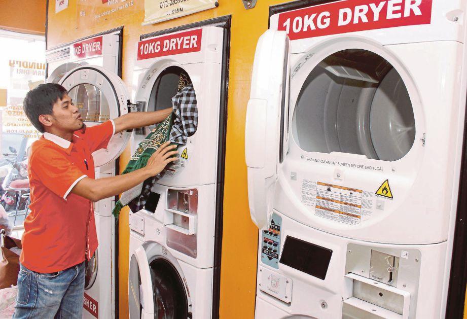 MOHD Sufian memasukkan pakaian kotor ke dalam mesin dobi di kedainya.
