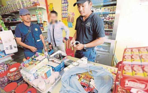 PENGUAT KUASA Kastam Kelantan memeriksa maklumat peniaga kedai runcit dipercayai menyimpan rokok putih di bawah kaunter.