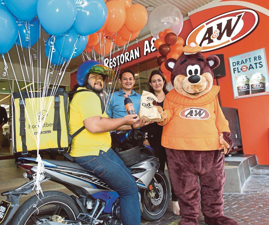 MOHD Hasmadi (dua dari kiri) bersama Ketua Pemasaran A&W Malaysia melancarkan khidmat penghantaran A&W, semalam.