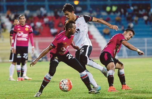 Pemain TFC II  Takhiyuddin (tengah) diasak dua  pemain Kelantan.