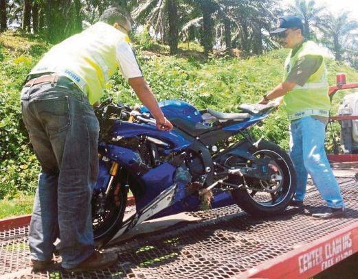 ANGGOTA polis mengangkat motosikal milik Tun Sufian yang terbabit nahas.