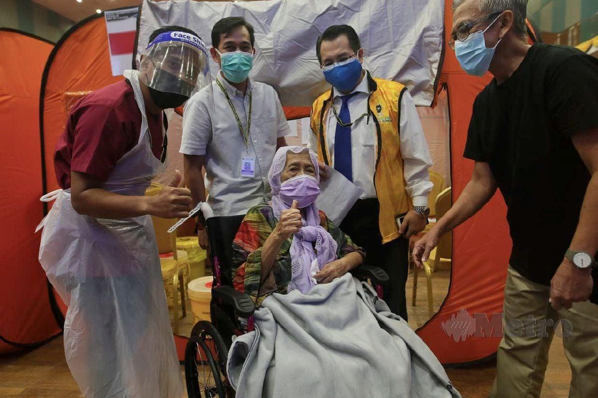 Jururawat Hospital Universiti Sultan Zainal Abidin (UniSZA), Mohd Borhan Hassan, 31(kiri) melakukan suntikan vaksin kepada neneknya, Fatimah Muda  berusia 102 tahun ketika ditemui di Pusat Pemberian Vaksin (PPV) UniSZA hari ini. FOTO GHAZALI KORI