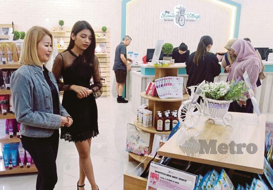 GAN (kiri) memberi penerangan mengenai produk jualan kepada Jeryl selepas pembukaan pusat jualan produk kecantikan kedua My Beaute Village di Aeon Mall Klebang.