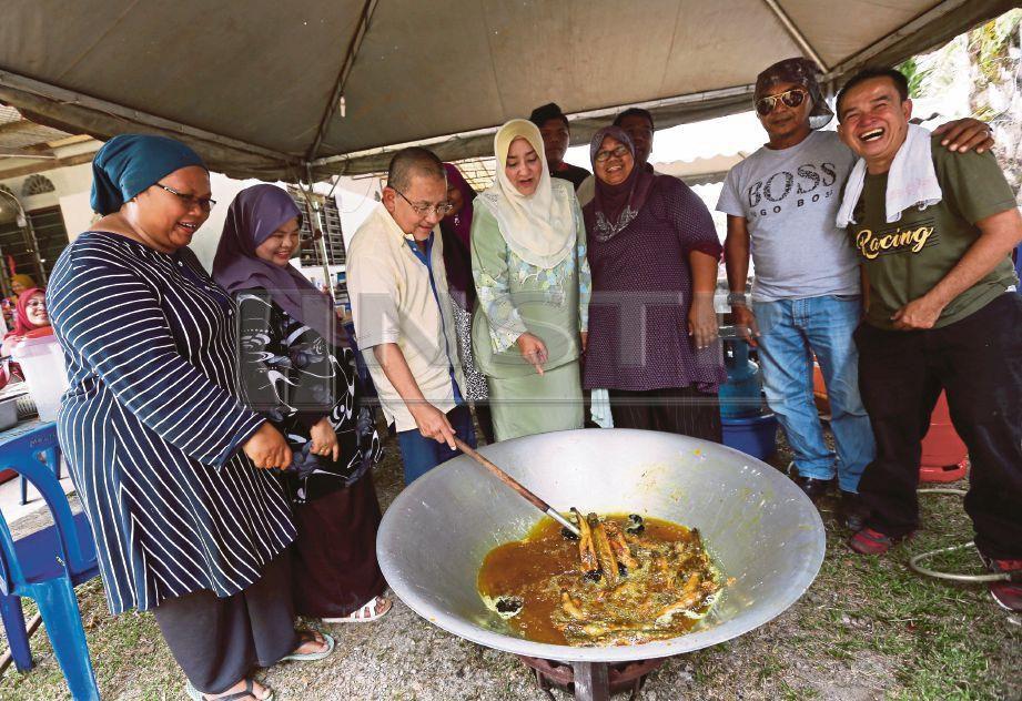 ISA bersama isteri, Puan Sri Bibi Sharliza Mohd Khalid membantu memasak ikan keli bersama penduduk setempat  di Kampung Pachitan, Port Dickson.