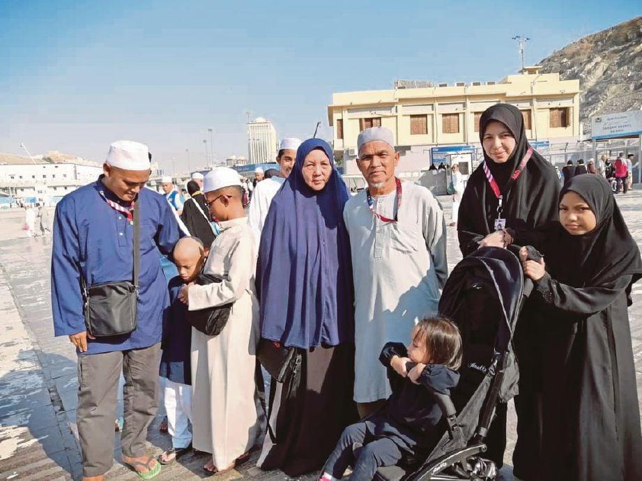 PENULIS (kiri) merakam gambar kenangan bersama jemaah lain ketika menziarahi beberapa lokasi bersejarah di sekitar Makkah.